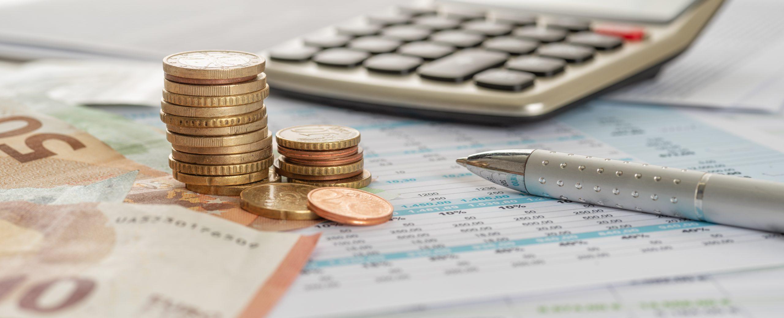 Geld mit Taschenrechner und Kugelschreiber